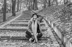 Young beautiful sexy girl model posing in the autumn park among fallen yellow leaves on the old stairs in a hat, coat, jeans and b Stock Photos