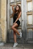 Young beautiful and girl with slim sun tanned attractive body is posing outdoor on the steps royalty free stock images