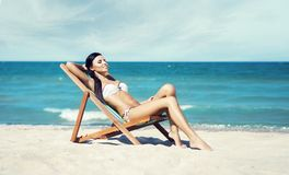 Young, beautiful, and sexy girl in white swimsuit relaxing on the beach. Traveling, resort, vacation, concept. Royalty Free Stock Photo