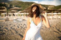 Young beautiful tanned brunette woman wearing hat and elegant dress standing on beach with wind fluttering hair. Stock Images