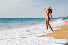 The young beautiful sexy woman in a bathing suit and a hat on a Stock Image
