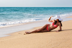 The young beautiful sexy woman in a bathing suit and a hat on a Stock Photos