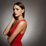 Young beautiful sexy woman.Beauty girl wearing jewelry.elegant lady in red dress Royalty Free Stock Photography