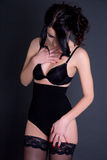 Young beautiful sexy woman in black lingerie over grey Stock Image
