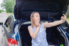 Young beautiful sexy woman at broken car with mobile phone, stan. Ding in the public road in forest area, calling for help with mobile phone. Broken vehicle in Stock Photos