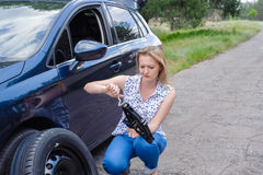 Young beautiful sexy woman at broken car with mobile phone, stan. Ding in the public road in forest area, calling for help with mobile phone. Broken vehicle in Royalty Free Stock Images