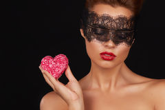 Young beautiful sexy woman with dark lace on eyes bare shoulders and neck, holding cake shape of heart to enjoy the taste and are Royalty Free Stock Photo