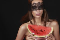 Young beautiful sexy woman with dark lace on eyes bare shoulders and neck, holding watermelon to enjoy the taste and are dieting, Stock Image