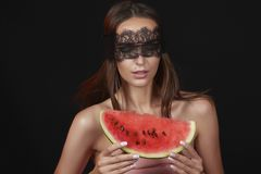 Young beautiful sexy woman with dark lace on eyes bare shoulders and neck, holding watermelon to enjoy the taste and are dieting, Royalty Free Stock Photography