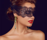 Young beautiful woman with dark lace on eyes bare shoulders and neck, jewelry earrings, feeling temptation, passion sex red l. Ips stock image