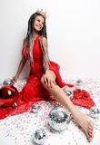 Young beautiful sexy woman in elegant red dress sitting in gold crown with christmas decoration ball and confetti. New year Holidays celebration concept Royalty Free Stock Images