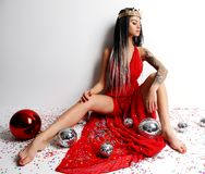 Young beautiful sexy woman in elegant red dress sitting in gold crown with christmas decoration ball and confetti. New year Holidays celebration concept Royalty Free Stock Photos