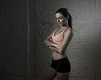 Young beautiful and sexy woman in fitness top and shorts with pe. Rfect abdomen posing isolated on dim light interior background in healthy lifestyle sport and Royalty Free Stock Image