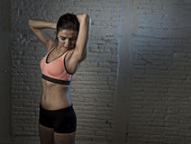 Young beautiful and sexy woman in fitness top and shorts with pe. Rfect abdomen posing isolated on dim light interior background in healthy lifestyle sport and Stock Photo