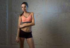 Young beautiful and sexy woman in fitness top and shorts with perfect abdomen posing. On dim light interior background in healthy lifestyle sport and diet Royalty Free Stock Image
