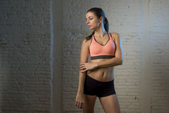 Young beautiful and sexy woman in fitness top and shorts with perfect abdomen posing. On dim light interior background in healthy lifestyle sport and diet Royalty Free Stock Photo
