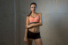 Young beautiful and sexy woman in fitness top and shorts with perfect abdomen posing. On dim light interior background in healthy lifestyle sport and diet Royalty Free Stock Photos
