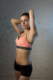 Young beautiful and sexy woman in fitness top and shorts with perfect abdomen posing. On dim light interior background in healthy lifestyle sport and diet Royalty Free Stock Photography
