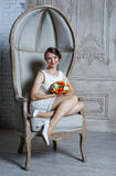 Young beautiful sexy woman with flowers in a chair on a couch Stock Image