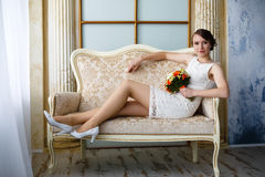 Young beautiful sexy woman with flowers in a chair on a couch Royalty Free Stock Images