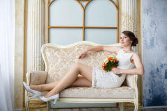 Young beautiful sexy woman with flowers in a chair on a couch Stock Images