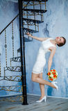 Young beautiful sexy woman with flowers and a spiral staircase Royalty Free Stock Photography