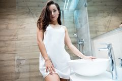 Free Young Beautiful Sexy Woman In White Gown Standing In The Bathroom While Doing Her Morning Routine Royalty Free Stock Images - 161276149