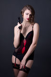 Young beautiful sexy woman in lingerie posing with gun over grey Royalty Free Stock Photos