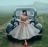 Young beautiful sexy woman in pin-up style clothes posing near black retro car. Polka dot white dress, vintage hairstyle