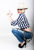Young beautiful woman in a plaid shirt jeans and a cowboy hat stock photo