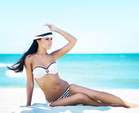 Young, beautiful and sexy woman relaxing on the beach Stock Photo