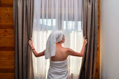 Young, beautiful, woman, after shower, closes curtain royalty free stock image