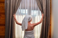 Young, beautiful, woman, after shower, closes curtain stock photo
