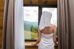 A young, beautiful, woman, after a shower, stands wrapped in a towel near the window in the hotel with a view of the mountain royalty free stock image