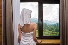 A young, beautiful, woman, after a shower, stands wrapped in a towel near the window in the hotel with a view of the mountain stock photography