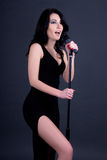 Young beautiful sexy woman singing with microphone over grey Stock Photo