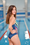 Young beautiful woman standing near blue water of swimming pool