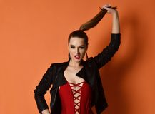 Young beautiful sexy woman standing in red summer fashion body vest and leather jacket hold braid on orange. Background Royalty Free Stock Photos
