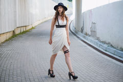 Young beautiful sexy woman wearing trendy outfit, white dress, black hat and leather swordbelt. Longhaired brunette. Posing in the city street on a sunny day Royalty Free Stock Images
