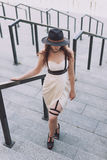 Young beautiful woman wearing trendy outfit, white dress, black hat and leather swordbelt. Longhaired brunette Royalty Free Stock Image
