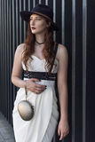 Young beautiful woman wearing trendy outfit, white dress, black hat and leather swordbelt. Longhaired brunette. Posing in the city street. Outdoor fashion Royalty Free Stock Image
