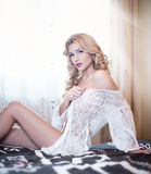 Young beautiful sexy woman in white lingerie posing challenging indoor staying on bed. Attractive sexy blonde wearing lingerie Stock Images