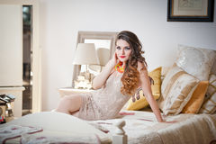 Young beautiful sexy woman in white short tight dress posing challenging indoor on vintage bed. Sensual long hair brunette in bedr Royalty Free Stock Photo