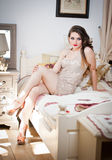 Young beautiful sexy woman in white short tight dress posing challenging indoor on vintage bed. Sensual long hair brunette Royalty Free Stock Photography