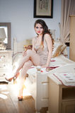 Young beautiful sexy woman in white short tight dress posing challenging indoor on vintage bed. Sensual long hair brunette Royalty Free Stock Photos