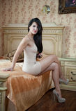 Young beautiful sexy woman in white short tight dress posing challenging indoor in vintage hotel room. Sensual brunette Royalty Free Stock Photography