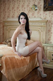 Young beautiful sexy woman in white short tight dress posing challenging indoor in vintage hotel room. Sensual brunette Royalty Free Stock Photo