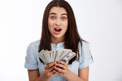 Young beautiful shoked business girl holding money looking at camera over white background Royalty Free Stock Images