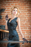 Young beautiful short hair blonde woman in black dress smoking a cigarette. Elegant romantic mysterious lady with movie star look. Red bricks wall on stock photography