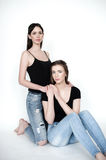 Young and beautiful sisters in friendship, sharing joy, trust, l. Ove, happiness and support, hugs, laughs and smiles wearing jeans holding hands Stock Images